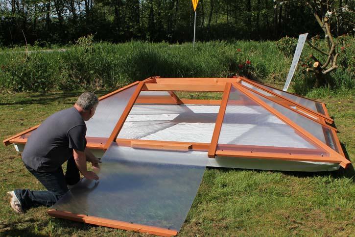 a man installing a hot tub enclosure roof panel