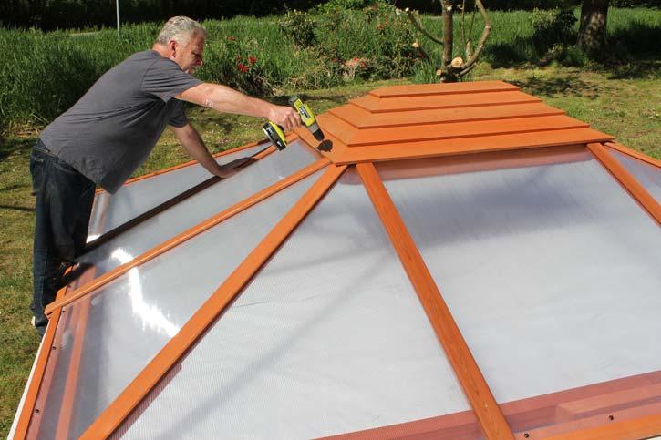 a man installing a hot tub enclosure roof panel and cap