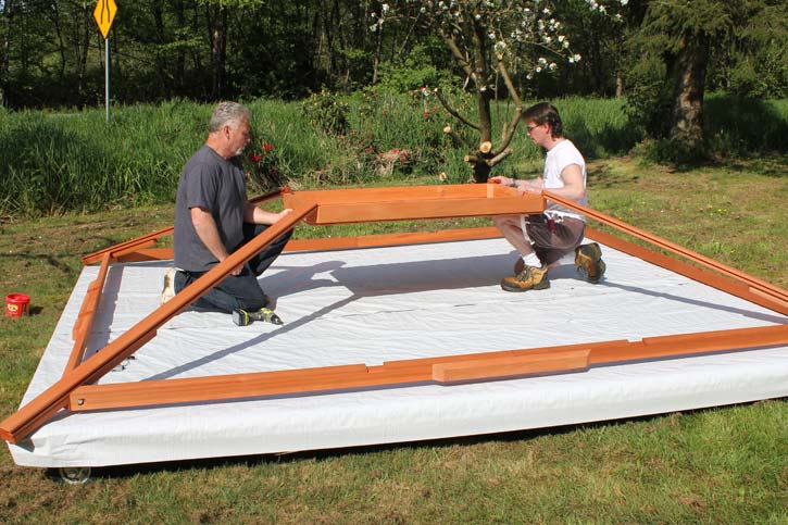 two men assembling a gazebo roof