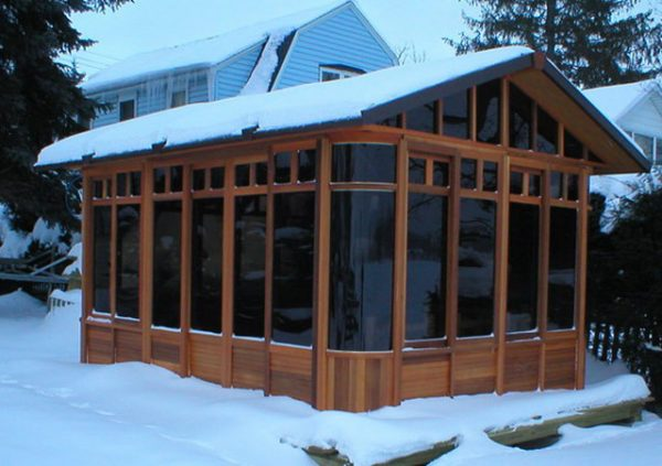 a chalet gazebo with snow on the roof