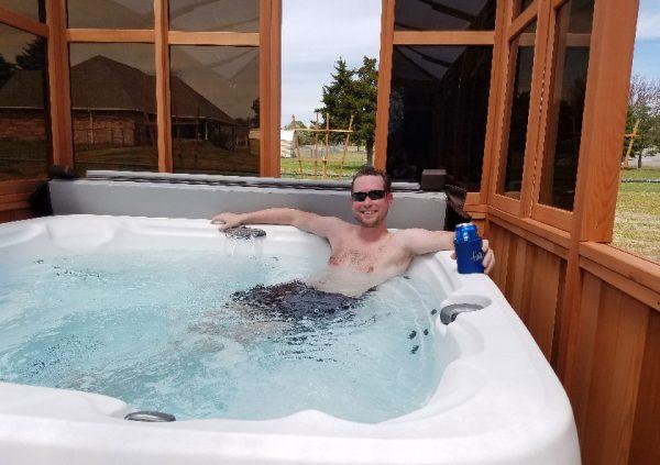 man on hot tub inside gazebo