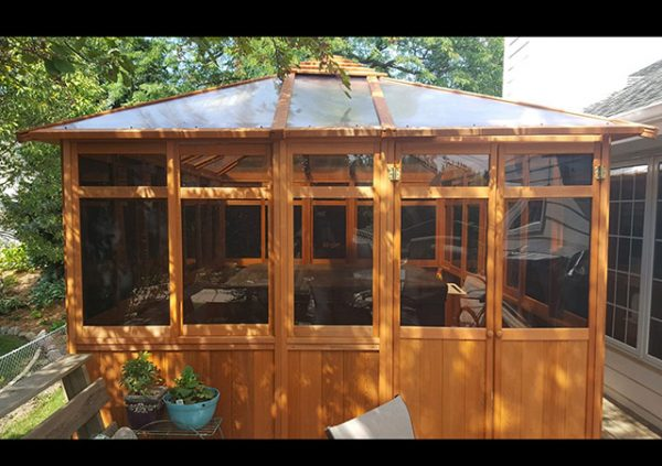 a hot tub enclosure with a transparent roof in the yard