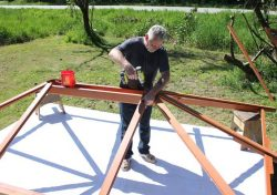 a man assembling a gazebo roof