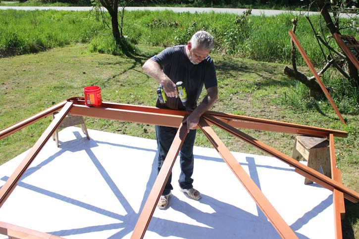 a man assembling a gazebo roof