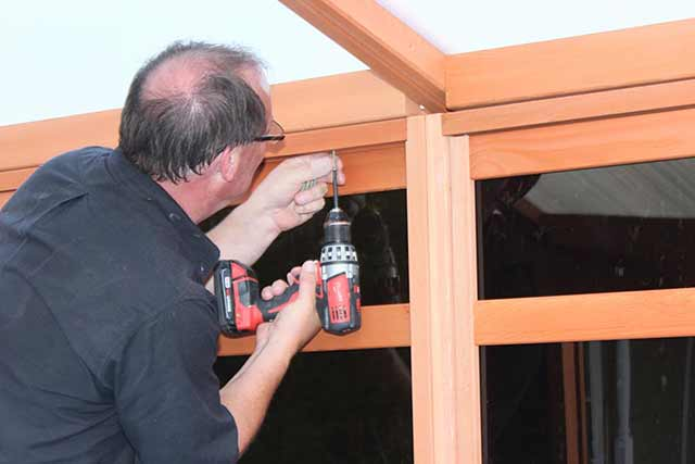 Man With Electric Screw Driver install a gazebo